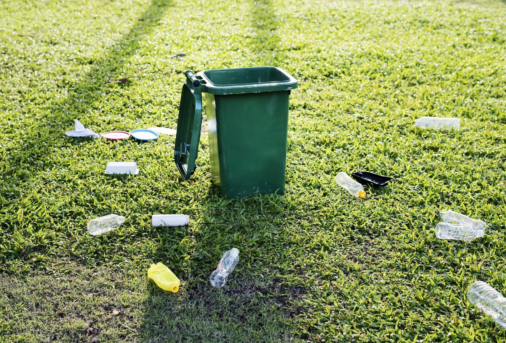 Garbage green trash bin on green grass field bottle Travel suitcase, boarding box how to throw garbage truck?Resource recovery or combustible waste?